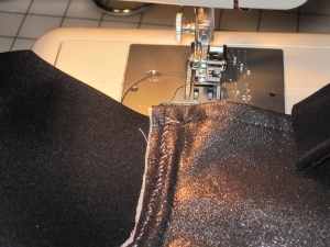 Stitch with zipper foot or hand stitch along underwire