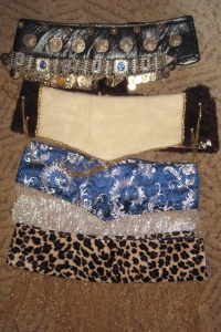 From top: base with coin belt attached, fake fur covered base for reindeer costume, damask-covered belt with silver glass bead fringe, animal pattern Velboa covered base with gold glass bead fringe. All made using the same technique.